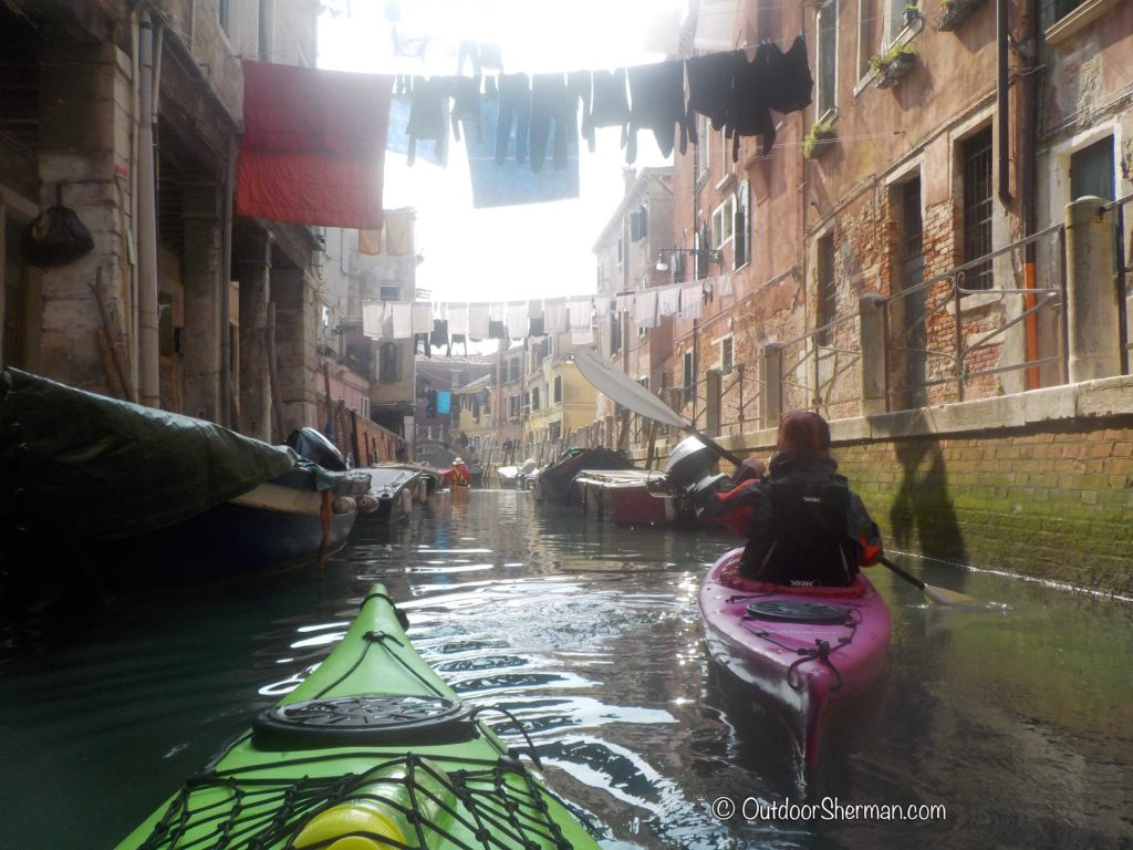 Kayaking through a quiet canal with hanging clothes